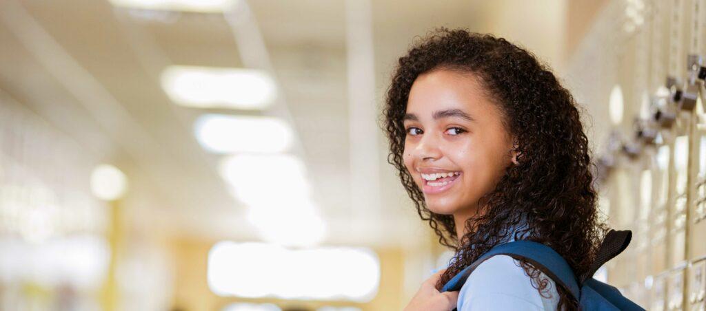 Smiling student in school hallway.