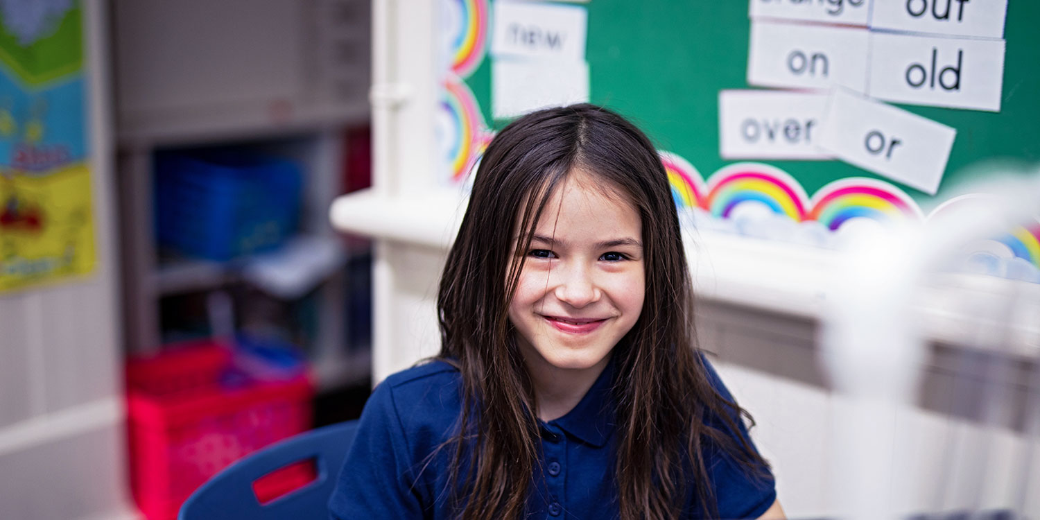 Smiling student in a classroom.